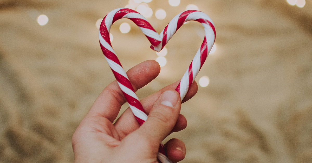 Christmas candy canes in the shape of a heart held in a man's hand