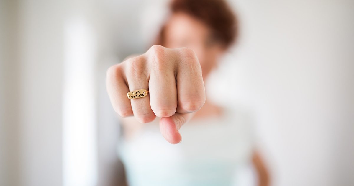 woman punching air with ring that says I am badass
